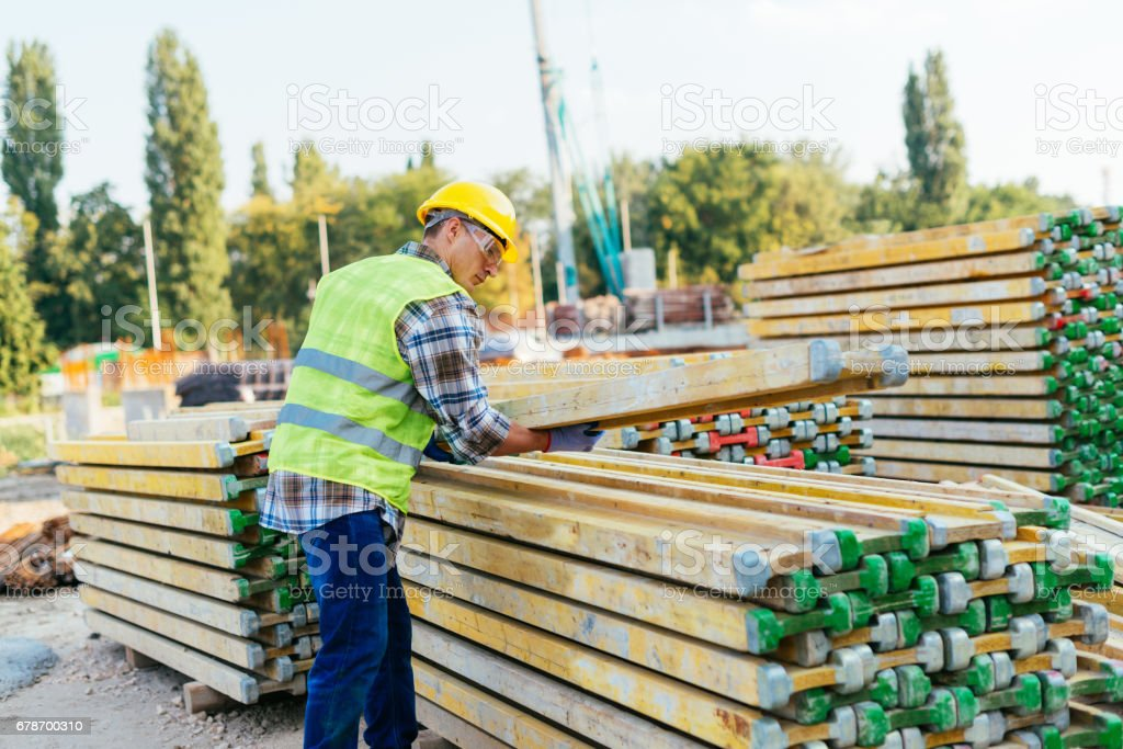 Manual construction worker working on construction platform, transferring construction material photo libre de droits