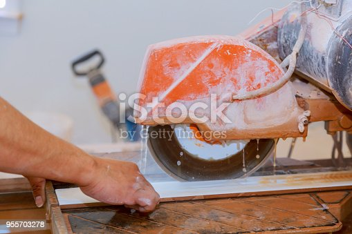 1138442636 istock photo Manual cutting of ceramic tiles on a special machine for cutting tiles. 955703278