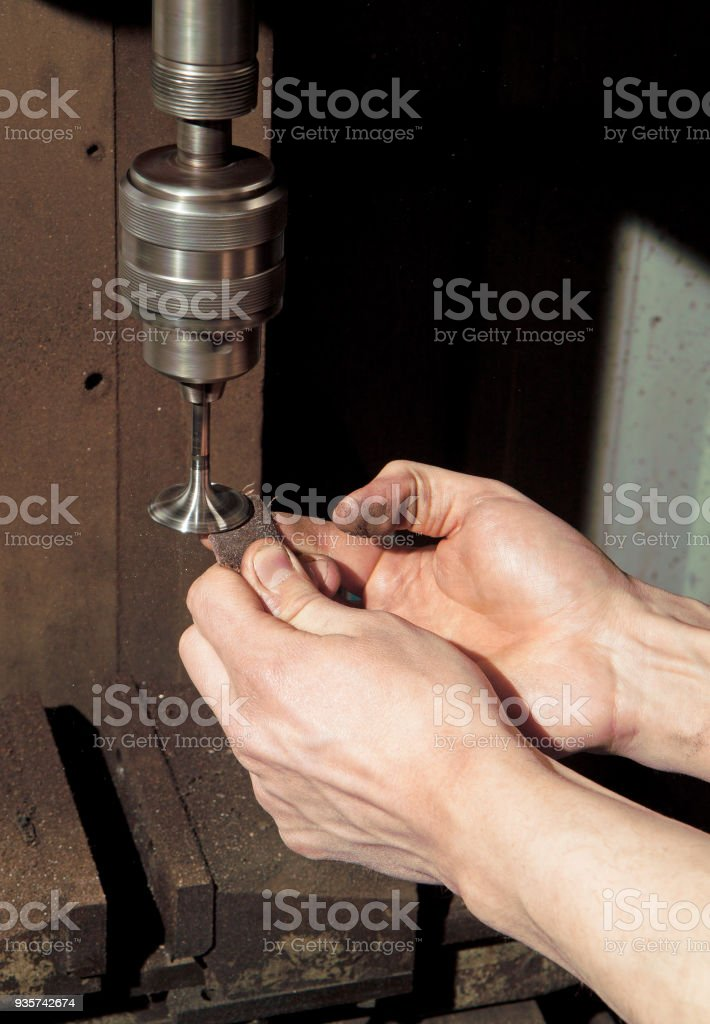 Manual grinding of an engine valve stock photo
