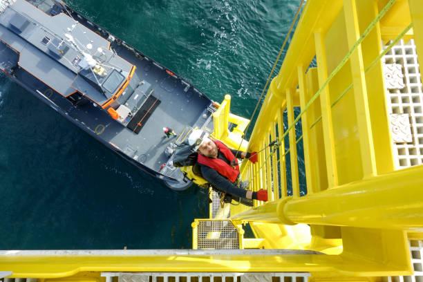hoge arbeider offshore klimmen naar beneden van windturbine ladder en overdracht drukvat op hem wacht - industrieel schip stockfoto's en -beelden