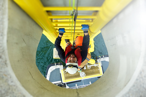 Manual high worker offshore climbing on wind-turbine on ladder and transfer vessel waiting under wind turbine