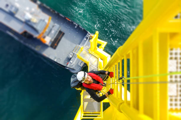 Manual high worker offshore climbing on wind-turbine on ladder Wind-turbine, offshore, worker, climbing, high up, boat, sea windmill stock pictures, royalty-free photos & images