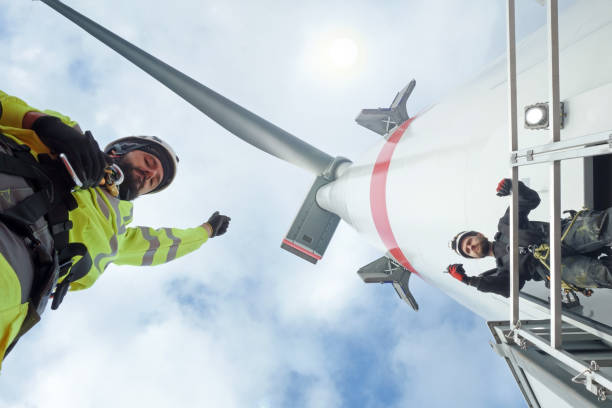Manual high workers working on biggest wind-turbine Wind-turbine, offshore, worker, climbing, high up, sun, big, north sea, borkum wind power stock pictures, royalty-free photos & images