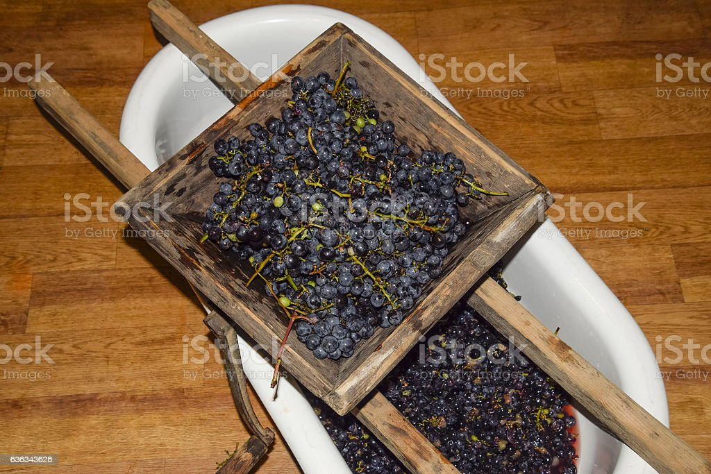 Manual mechanism for crushing grapes stock photo