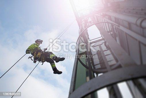 Técnico de acceso manual de cuerdas - trabajador abseil de la torre - antena en los rayos solares