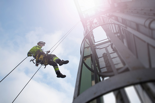 Manual rope access technician - worker abseil from tower - antenna in sun beams