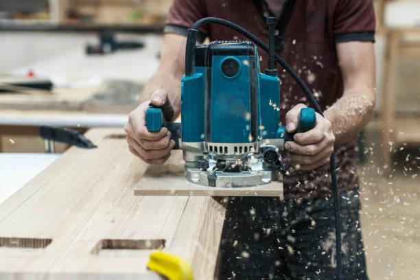 manuelle holz konzept. nahaufnahme foto von tischler handwerk handwerker mit elektrowerkzeug in händen machen möbel in garage oder arbeitszimmer beschnitten - tischlerarbeit stock-fotos und bilder