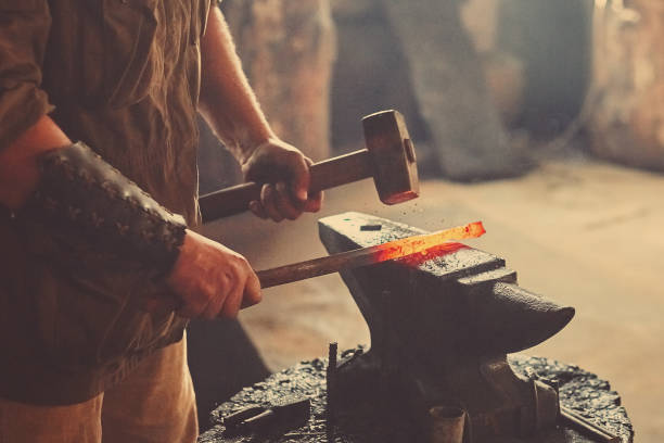 Manual work of a blacksmith in a blacksmith Shop. Hammer blows on the iron billet on the anvil. Forging sword blades is a retro weapon stock photo