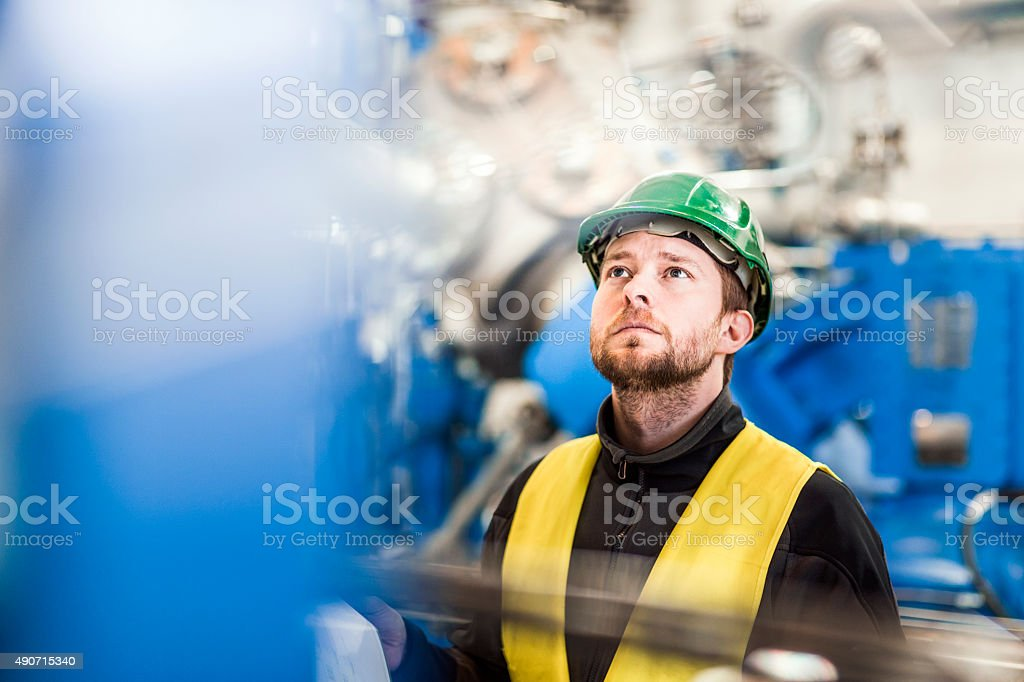 Manual worker analysing machinery in factory stock photo