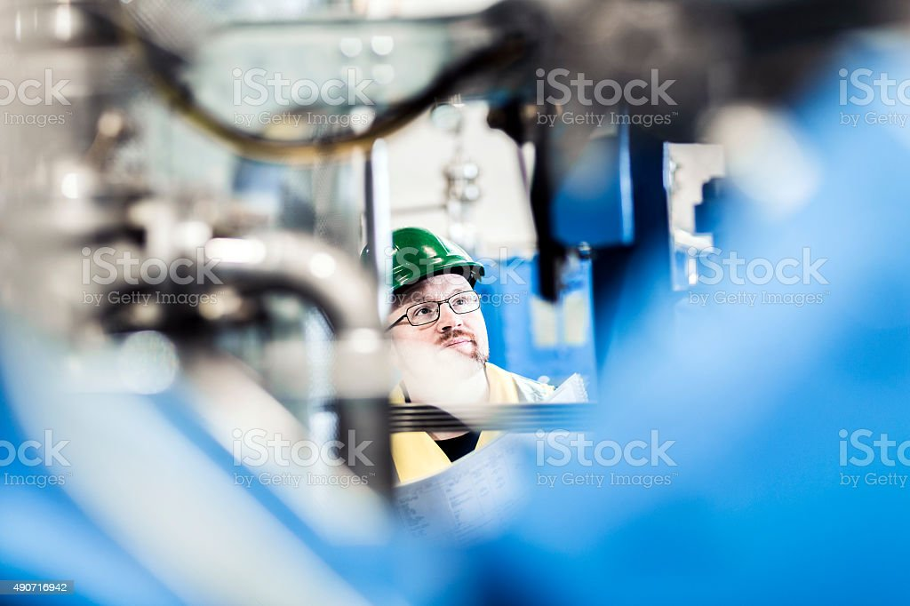Manual worker analysing machines at factory stock photo