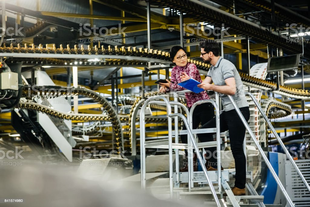 Manual Worker And Female Engineer In A Factory stock photo