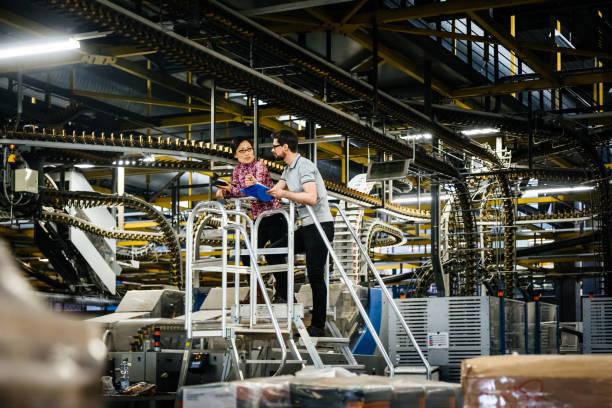 Trabajador manual y la Ingeniera en una fábrica de - foto de stock