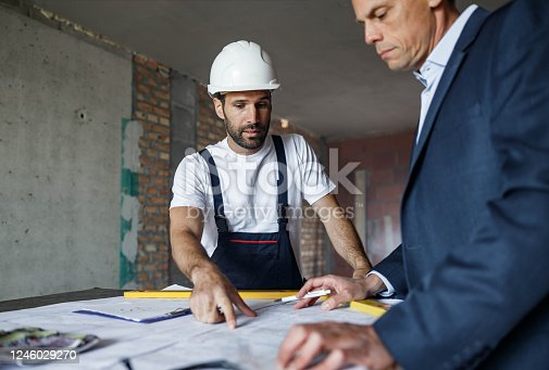 891274328 istock photo Manual worker and foreman going through housing plans at construction site. 1246029270