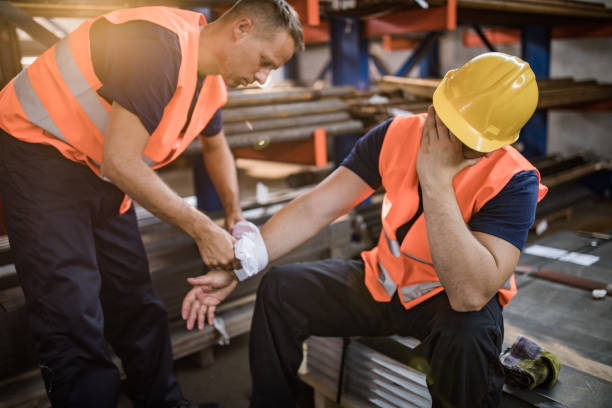 Manual worker assisting his colleague with physical injury in steel mill. Manual worker feeling pain after having an injury at work while his colleague is helping him. misfortune stock pictures, royalty-free photos & images