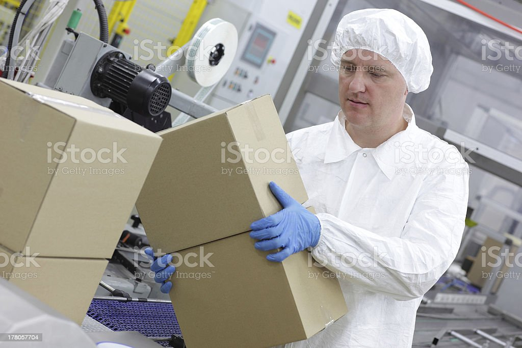manual worker at production line dealing with boxes royalty-free stock photo