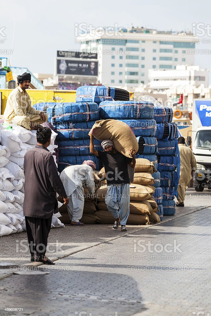 Manual worker at the Dubai Creek carying a big bag. royalty-free stock photo