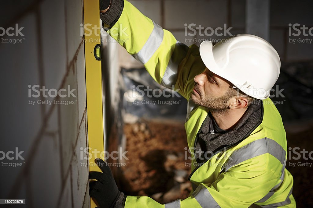 Manual worker checking vertical surface of a wall royalty-free stock photo