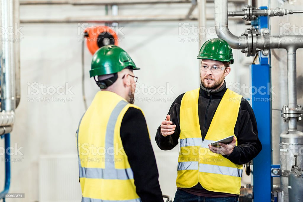 Manual worker discussing with colleague in factory stock photo