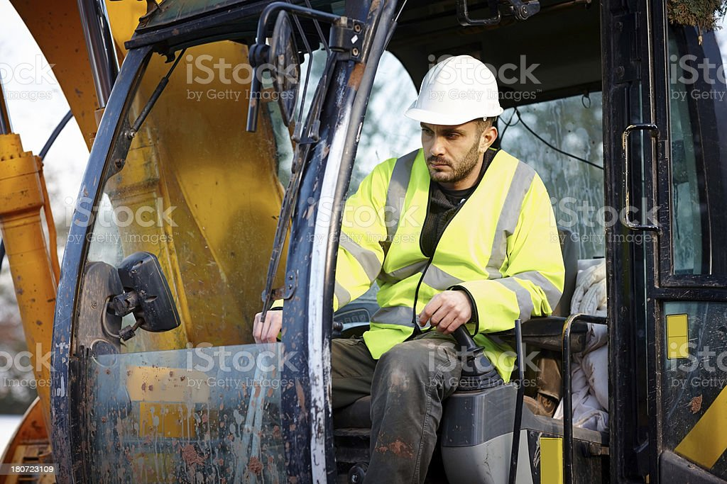 Manual worker driving excavator at construction site royalty-free stock photo