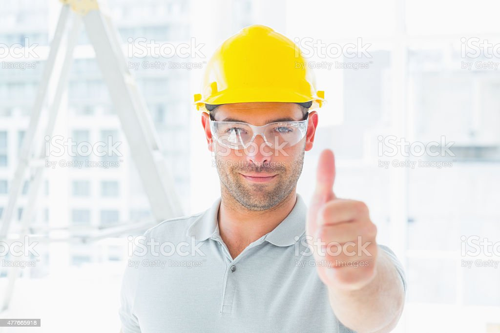 Manual worker gesturing thumbs up at site stock photo