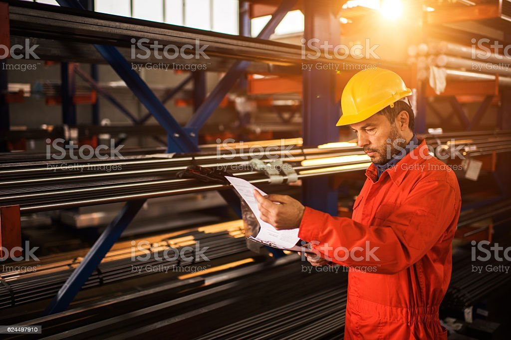 Manual worker going through paperwork in aluminum mill. stock photo
