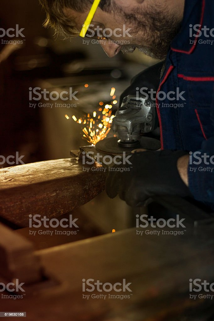 Manual worker grinding steel table in production hall. stock photo