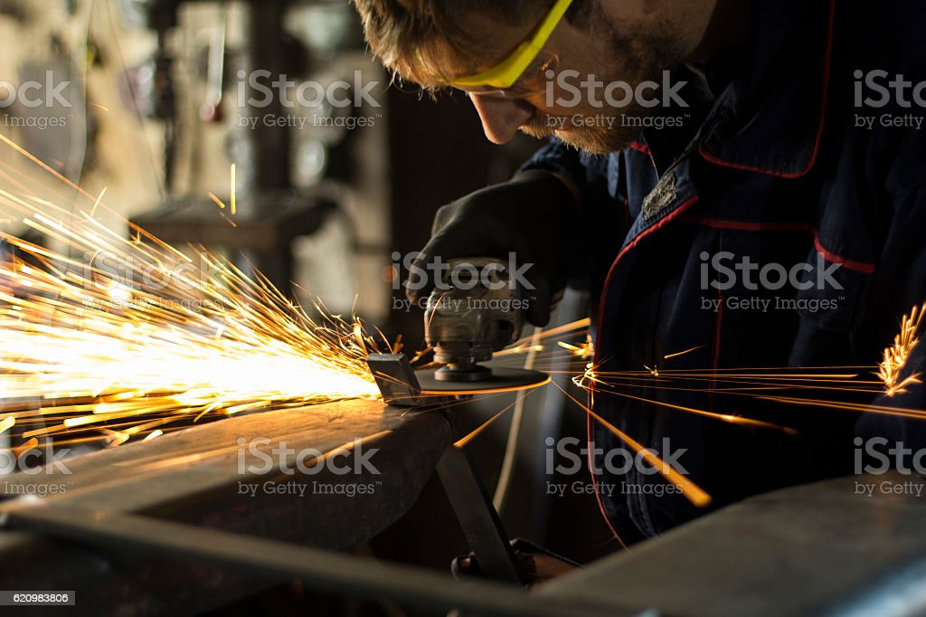 Manual worker grinding steel table in production hall. foto royalty-free