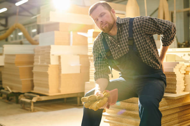 Manual worker having pain in back Tired handsome bearded manual worker with closed eyes sitting on stack of wooden plank and massaging lower back while feeling pain in back place of work stock pictures, royalty-free photos & images