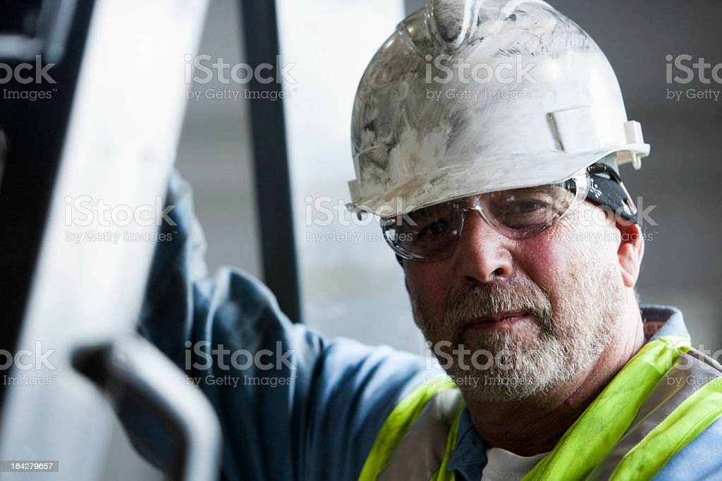 Manual worker in hard hat and safety glasses stock photo