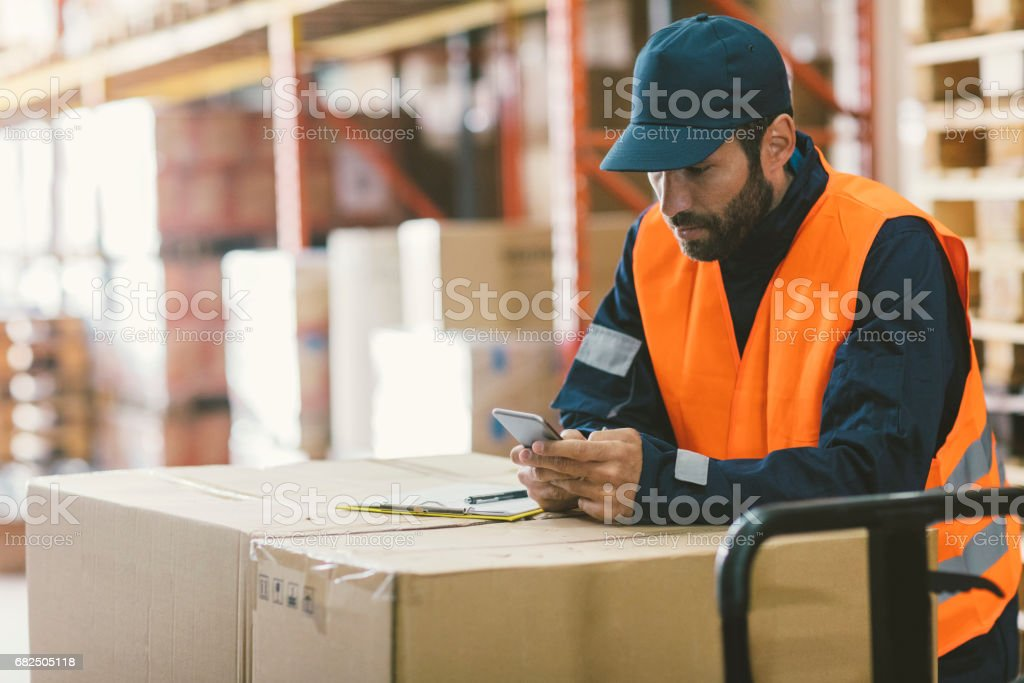 Male manual worker in warehouse checking merchandise. Writing...
