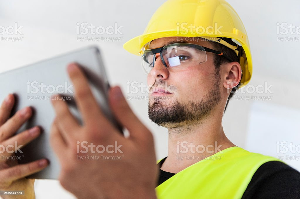 Manual worker  in yellow helmet using a digital tablet royalty-free stock photo