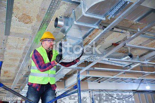 Manual Worker  installing air conditioner in building.