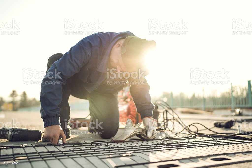 Manual worker installing metal part on road construction at sunset. stock photo