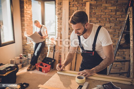 istock Manual worker making measurements on a piece of wood at construction site. 921965966