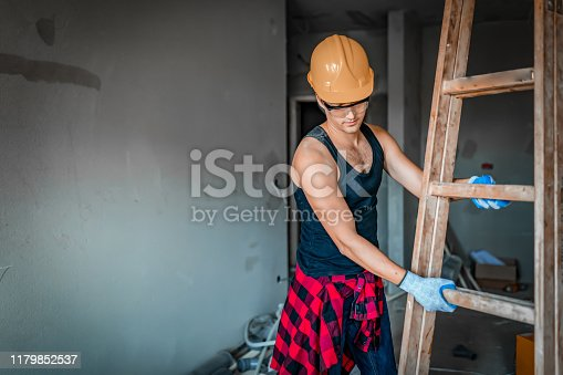 Young maintenance worker with orange safety helmet carrying step ladder at construction site. Civil engineering, Architecture builder and building service concepts stock photo