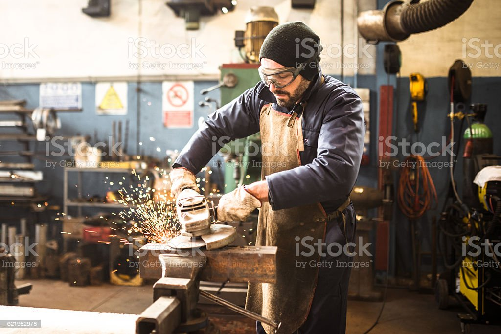 manual worker on a workshop with the grinder - foto de stock