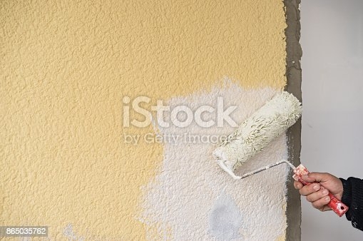 835790922istockphoto Manual worker painter at work, painting wall with new color 865035762