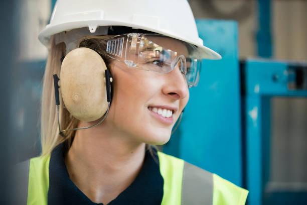 Manual Worker A close-up shot of a beautiful young woman at work, she is wearing a hard hat, protective ear muffs,  protective eyeglasses and a hi-vis jacket. protective eyewear stock pictures, royalty-free photos & images