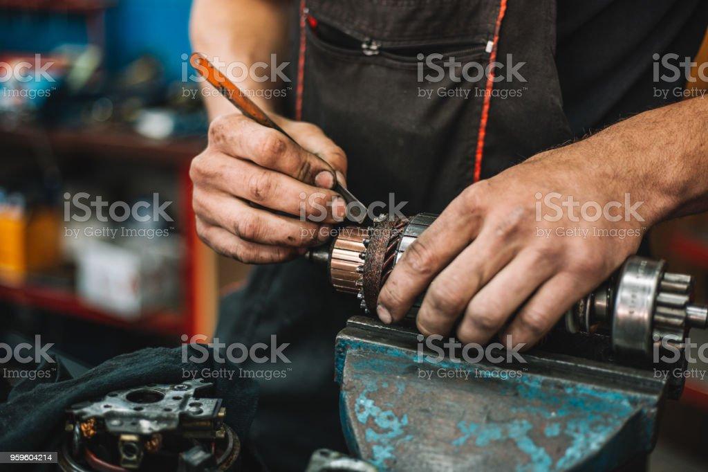 Manual worker repairing electric motor in a workshop stock photo