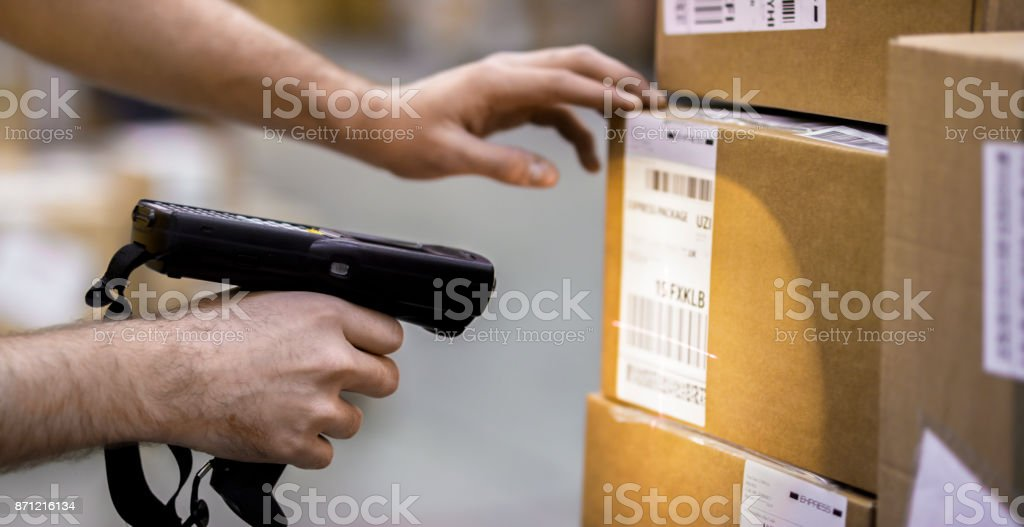 Manual worker scanning cardboard box stock photo