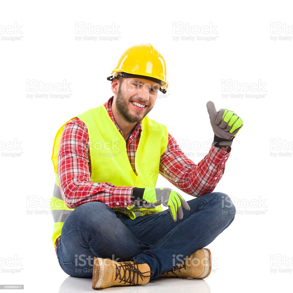 Manual worker sitting on floor and showing thumb up stock photo