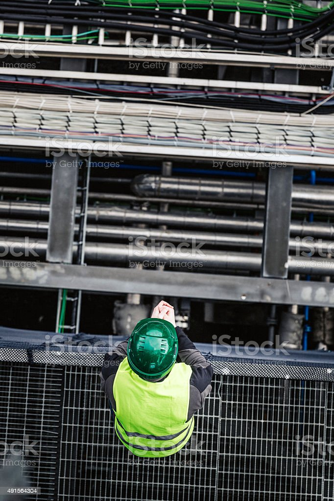 Manual worker standing on metal grate in factory stock photo