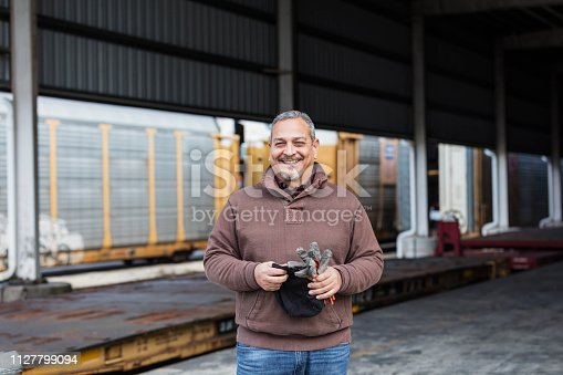 A mature Hispanic man in his 40s with a beard, a manual worker at a shipping port, standing outdoors in a storage area.