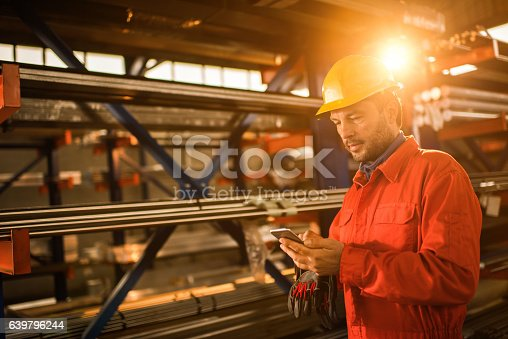 Mid adult worker standing in a factory and reading a text message on smart phone.
