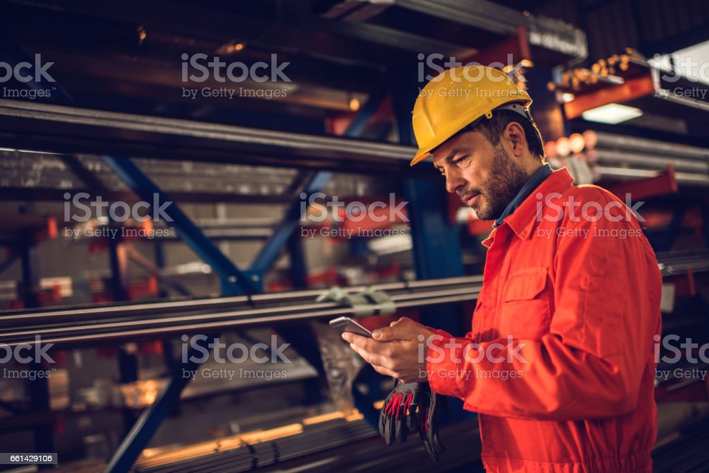 Manual worker text messaging on cell phone in aluminum mill. stock photo
