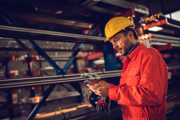 Arbeiter-SMS auf Handy in Aluminium-Mühle. – Foto