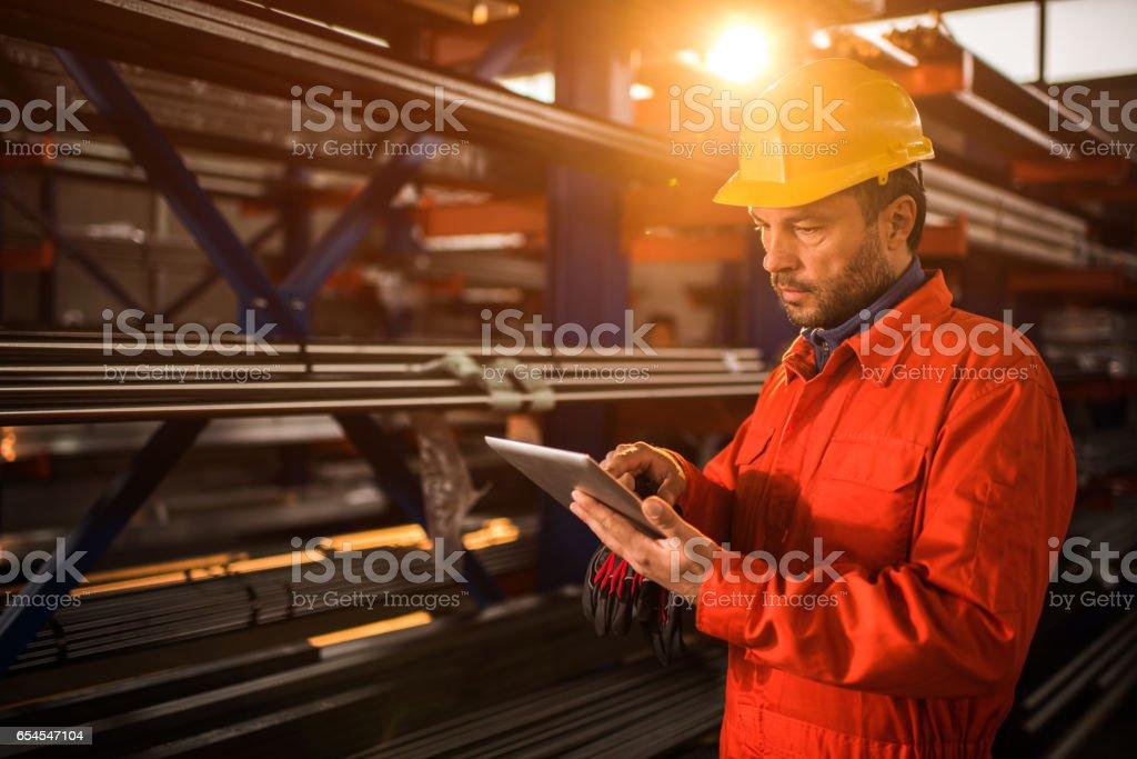 Manual worker using digital tablet in industrial building. stock photo