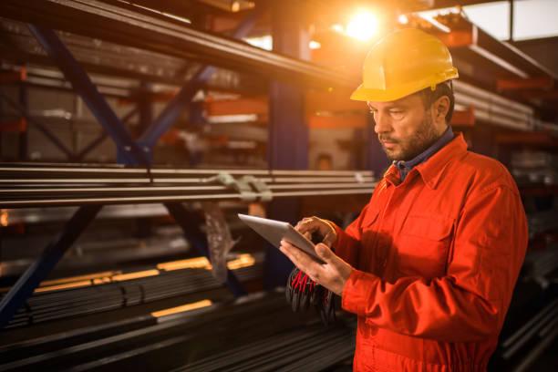 ouvrier en bâtiment industriel à l'aide de tablette numérique. - palm photos et images de collection