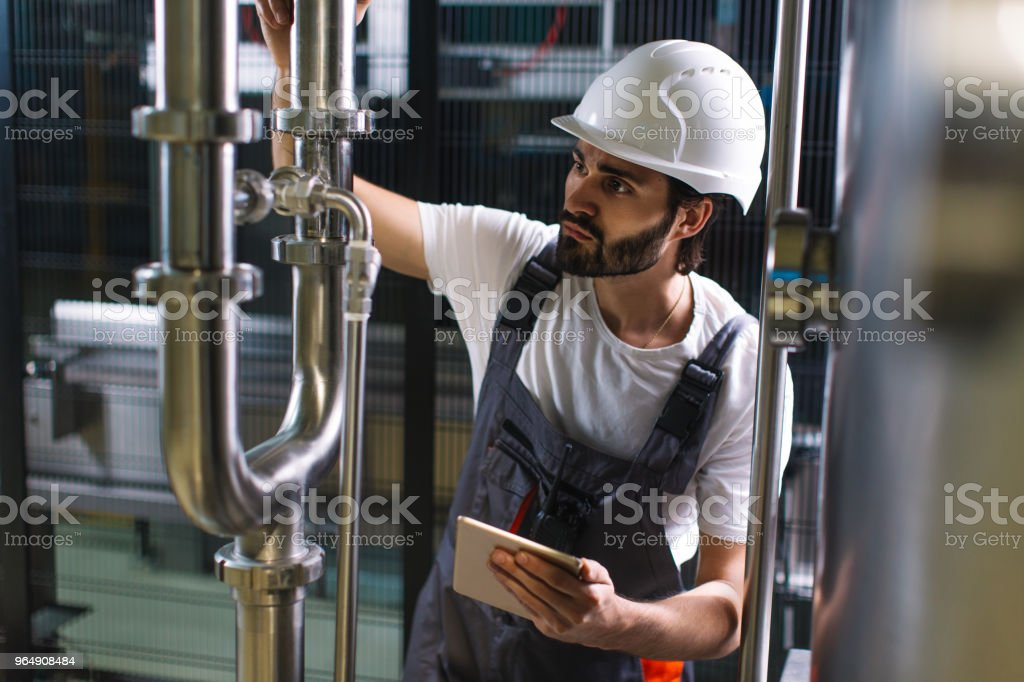 Manual worker using digital tablet in industrial building royalty-free stock photo