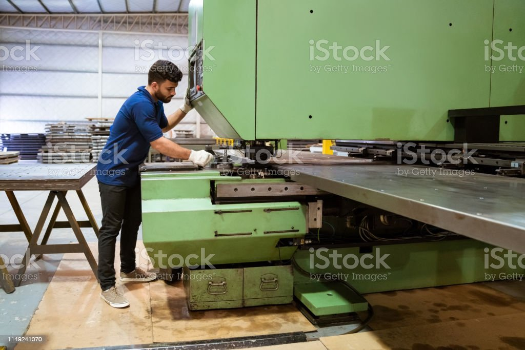 Manual worker using puller machine in industry Full length of male engineer using puller machine. Young trainee is working in manufacturing industry. He is in uniform at factory. 20-24 Years Stock Photo